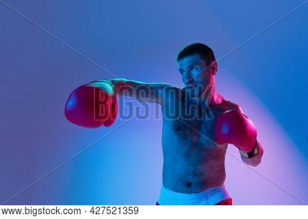 Portrait Of Caucasian Man, Professional Boxer In Sportwear Boxing On Studio Background In Gradient N