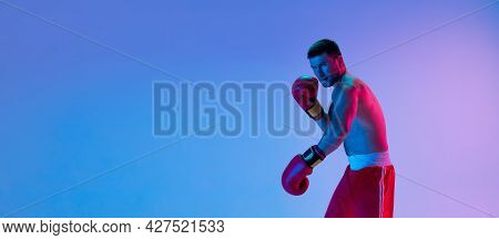 Flyer. One Man, Professional Boxer In Sportwear Boxing On Studio Background In Gradient Neon Light.