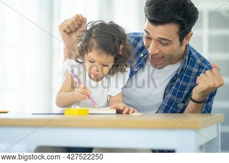 Happy Family: Father Teaching His Cute Little Daughters' Study. Family Creativity And Education At C