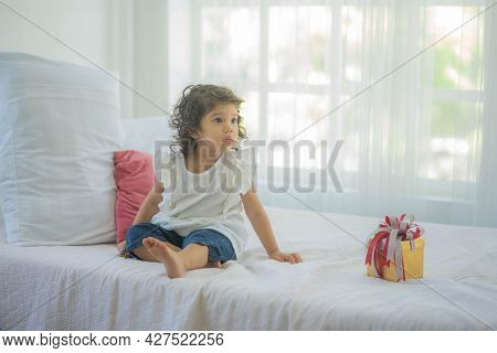 Cute Little Child Sitting On Bed With Gift Box At Home, Take Congratulations On Your Birthday.
