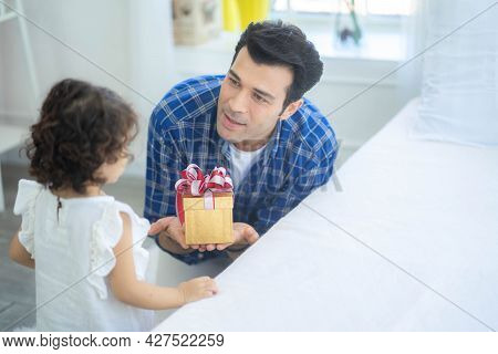 Handsome Young Father Is Giving A Gift Box To His Cute Little Daughter, Love Family Day Parenthood C