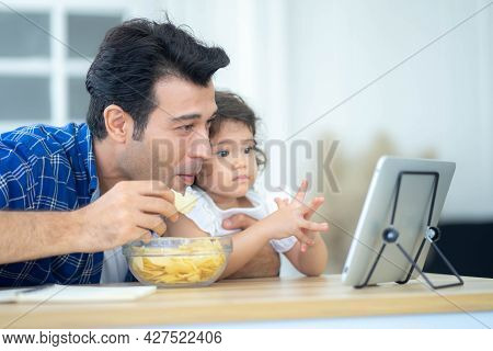 Father And Daughter, Happy Family Spending Time At Home And Looking Something Fanny On Tablet.