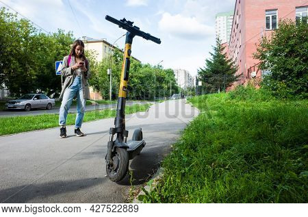 Novosibirsk, Russia - 20 July, 2021: Young woman using mobile phone to unlock electric scooter, Electric urban transportation in Siberia in summer