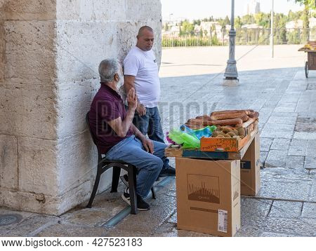 Jerusalem, Israel, July 17, 2021 : A Pretzel Seller Talks To A Passer-by While Waiting For Buyers At