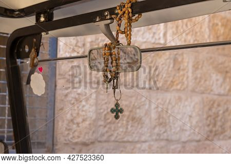 Rosary Beads, A Cross, A Crucifix And The Star Of David Hang On The Mirror Of A Car Near The Entranc