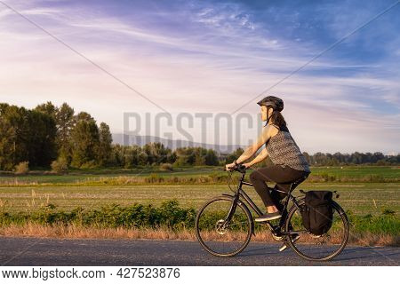 Adventurous White Cacasusian Woman Riding A Bicycle On A Road. Sunny Summer Sunset Art Render. Barns