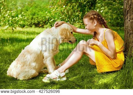 Cheerful cute girl playing with her pet dog in a sunny summer park.