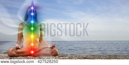 Yoga meditation outdoors. Glowing seven all chakra. Woman sits in a Upward Salute pose on beach sunset view, Kundalini energy. girl practicing.