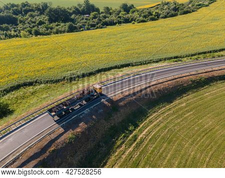 Red tipper truck on street road highway transportation. Semi-truck countryside aerial view.