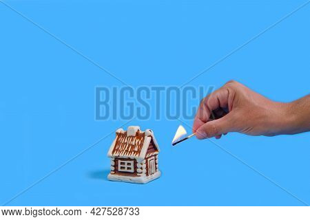 House And A Lit Match In His Hand On A Blue Background, Arson Causing Intentional Damage