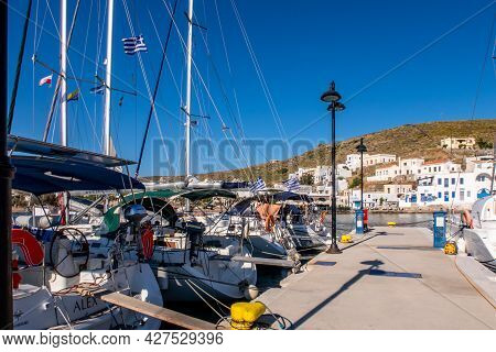 Loutra, Greece, 03.06.2019. Pier In Loutra Marina Kythnos With Sailing Boats Moored, Lanterns And Tr