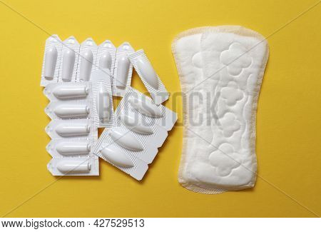 Sanitary Pads And Vaginal Suppositories On A Yellow Background, Top View, Flat Lay. The Concept Of W