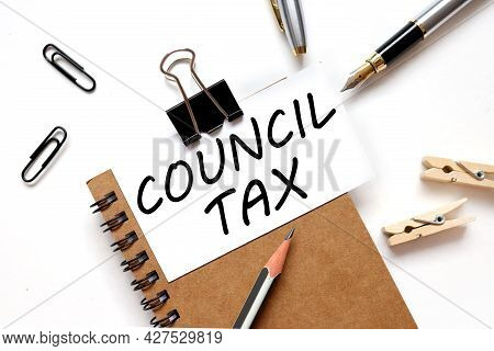 Council Tax. The Inscription On The Business Card Is Attached To The Notebook.