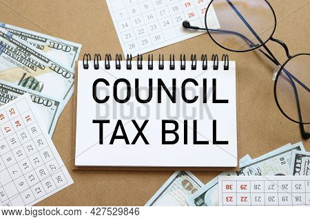 Council Tax Bill. Text On White Notepad Paper Near Calendar On Wood Craft Background