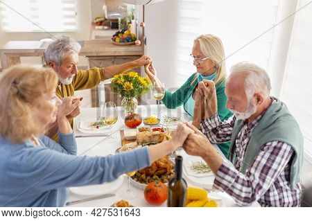Group Of Senior People Celebrating Thanksgiving Together At Home Over Traditional Dinner, Praying An