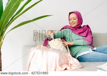 Middle eastern woman in headscarf holding cellphone while sitting on sofa at home
