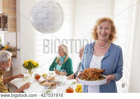 Senior Friends Gathered Around Table, Celebrating Thanksgiving, Having Dinner Together At Home, Host