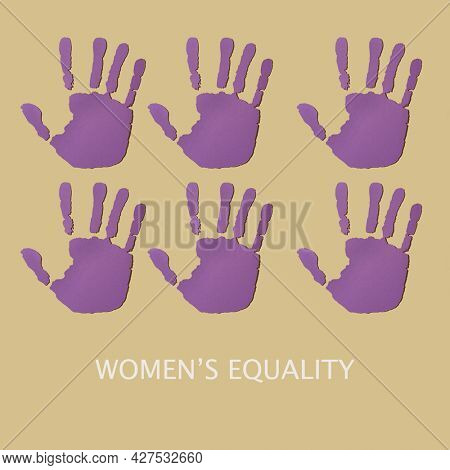 text womens equality and some hands cut out in a violet paper, depicting the idea to stop the violence against women or raising the hand for the womens rights, on a pale brown background