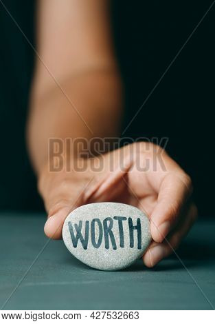 a caucasian man shows a cobblestone with the text worth written in it, on a dark gray surface