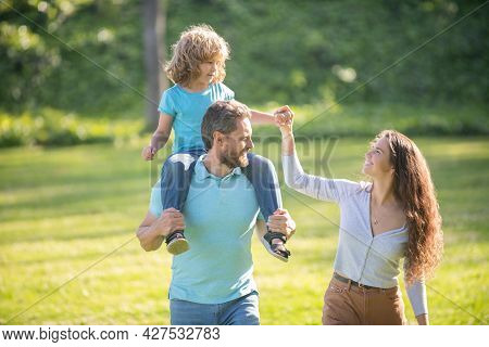 Foster Care. Foster Parents And Son. Mother And Child Riding Piggy Back On Father. Adoptive Family
