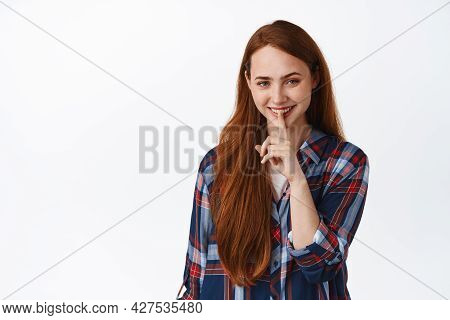 Image Of Pretty Caucasian Girl With Red Hair Smiles, Make Shush, Press Finger To Lips, Quiet Or Tabo