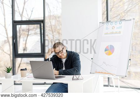 A Man Dressed In Casual Clothes Works In The Office With A Laptop And Expresses Sad Emotions.