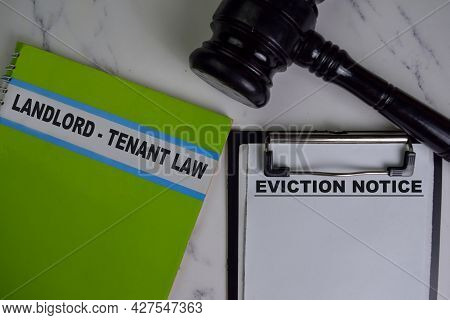 Eviction Notice On Document And Book Landlord-tenant Law Isolated On Wooden Table.