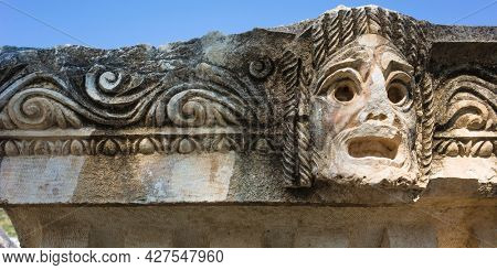 Theatrical mask stone carving of ancient town of Myra in Lycia region, Antique culture, Ruins of ancient city of Myra in Demre, Turkey