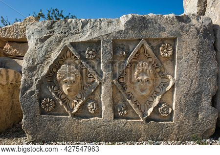 Ancient Lycian stone slab with portraits of people carved in stone in geometric form with floral decoration, Ruins of ancient city of Myra in Demre, Turkey