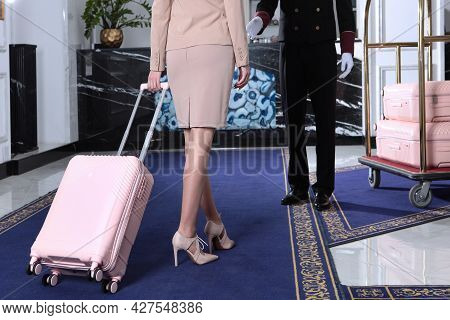 A Business Woman Arrived At The Hotel. A Woman Holds A Suitcase In Her Hand. Doorman In Uniform. Mee