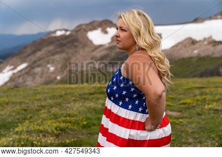 Patriotic Young Woman Wearing An American Flag Dress Looks Concerned At Beartooth Highway In Wyoming