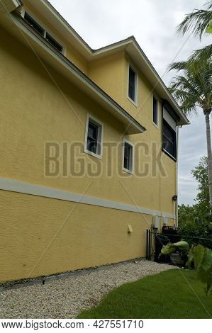 Wide Angle View Of Exterior Of Generic Florida Building Or Home With Palm Trees