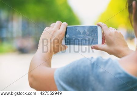Woman taking photo on a street with smartphone