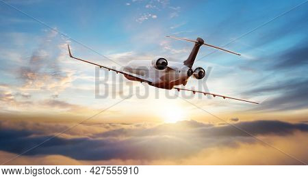 Private Passengers jetliner flying above clouds in sunset light. Concept of fast travel, holidays and business.