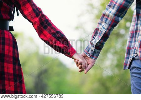 Unrecognizable Romantic Couple Holding Hands In Nature. Close-up Shot Of Man And Woman With Hand To