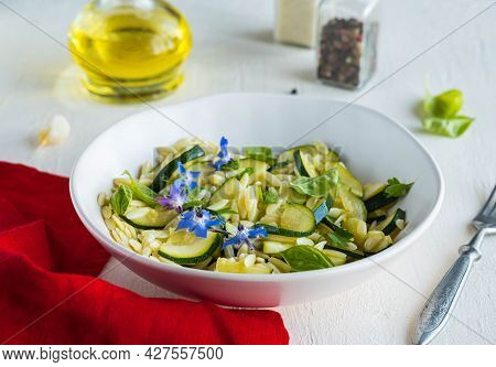 Salad With Orzo Pasta, Fried Zucchini And Garlic With Olive Oil Dressing In A Ceramic Bowl On A Ligh