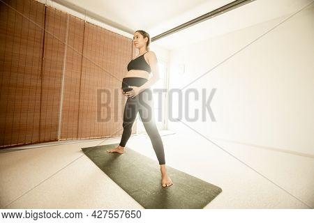 young pregnant woman practicing maternity yoga