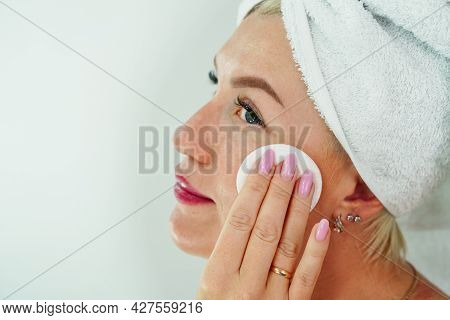 A Woman Removes Makeup With A Napkin In The Bathroom, Wipes Her Face With A Cotton Pad. Cleansing An