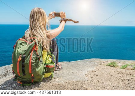 Woman hiker, hiking backpacker traveler camper with her phone camera on the top of mountain in sunny day under sun light. Beautiful sea landscape view.
