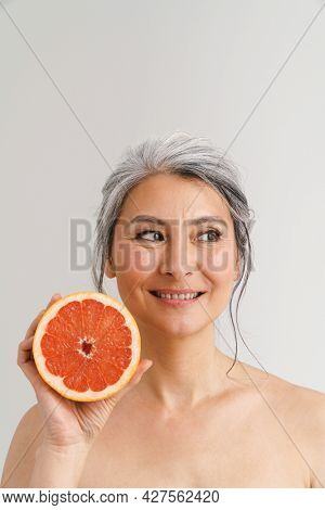 Mature shirtless woman with grey hair showing grapefruit isolated over white background
