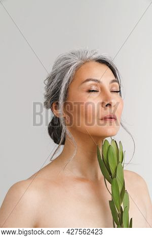Mature shirtless woman with grey hair posing with plant isolated over white background