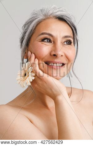 Shirtless woman with grey hair smiling while posing with gerbera isolated over white background