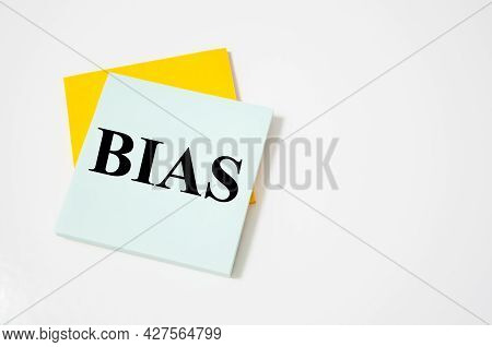 Bias Text Written On A White Notepad With Colored Pencils And A Yellow Background