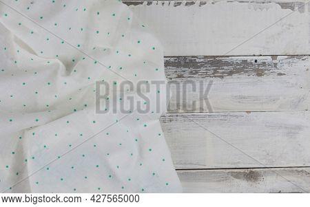Green polka dot textile on vintage white wooden table background. Wooden table with white textile