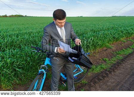Businessman with a bicycle takes documents from the briefcase in a green grass field - business concept for freedom, vacation or freelance. Beautiful spring nature.