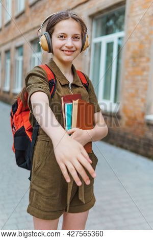 Teen schoolgirl on the way to the school. She is listening to music on headphones and holding a book. Education and back to school concept