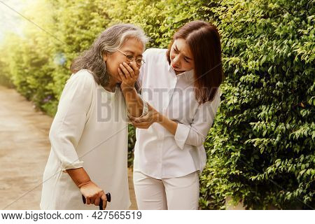 Elderly Health Care Concept : Daughter Caring For An Elderly Mother, Chronically Ill With Respirator