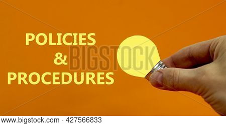 Policies And Procedures Symbol. Businessman Holds Yellow Shining Light Bulb. Words 'policies And Pro