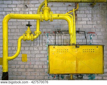 Yellow Natural Gas Pipes, Valves And Gas Meter In A Outdoor Anti-vandal Metal Box. There Is An Isola