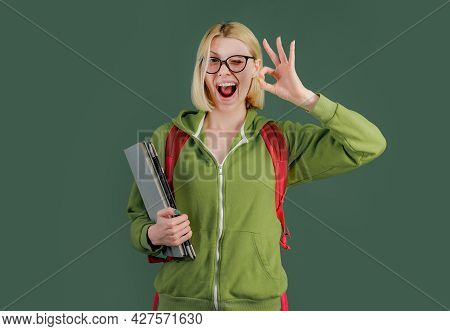 Young Funny Student In Glasses And With Book Over Green Chalkboard Background. Portrait Of Creative